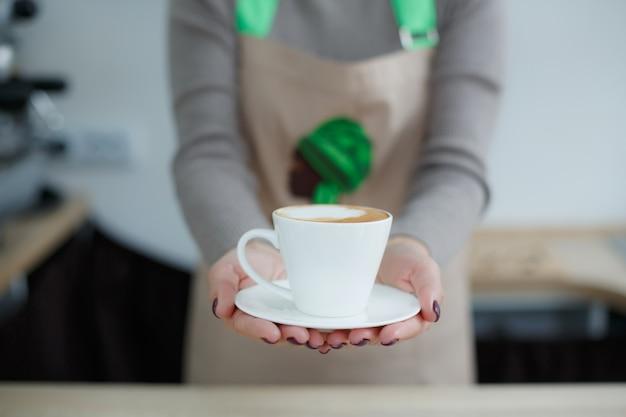 Barista no avental no café dar café fresco acabado de fazer ao cliente