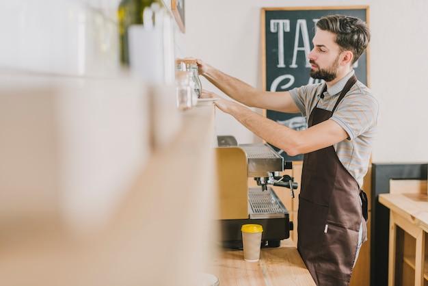 Barista organizando prateleiras no café