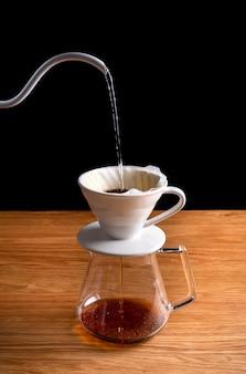 Barista preparando água para servir em grãos de café moídos contidos em um papel de filtro