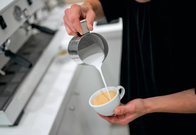 Barista profissional derramando leite vaporizado em uma xícara de café na cafeteria.