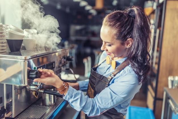 Barista profissional e bem vestida cozinhando a vapor da máquina de café em um café.