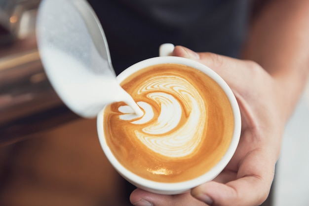 Barista que faz a arte do latte ou do cappuccino com espuma espumoso, copo de café no café.