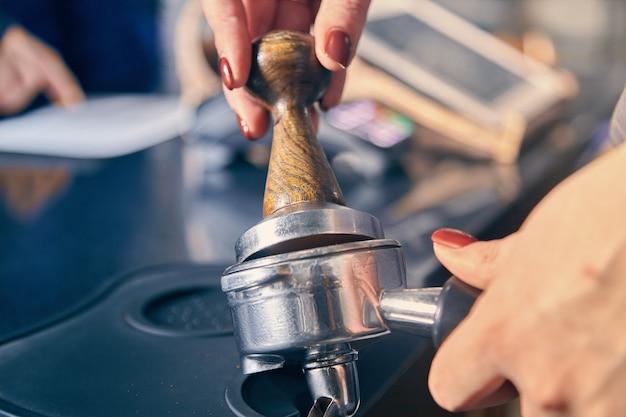 Barista segurando portafilter e adulteração de café. café preparar conceito. mão do barista em frente à caixa. barista pressiona café moído usando adulteração. imagem enfraquecida. copie o espaço para o projeto. cafeteria
