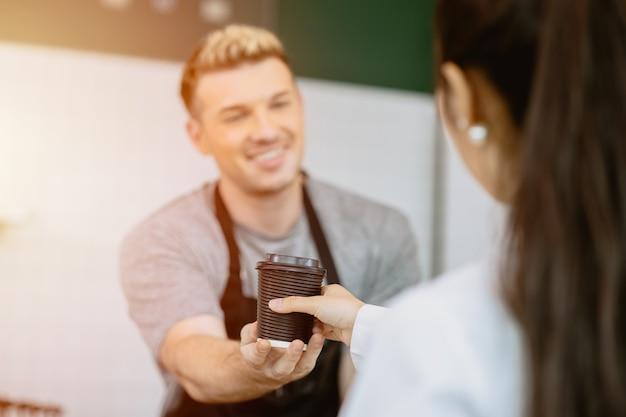 Barista serve o café no balcão para o cliente com espírito de serviço feliz e sorridente