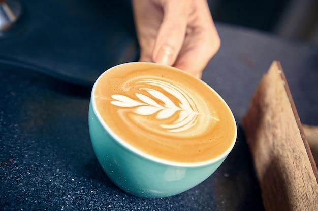 Barista servindo café na casa de café. mulher dando café com leite ou cappuchino ao cliente atrás do balcão. conceito de restaurante café. imagem enfraquecida. copie o espaço. café fresco