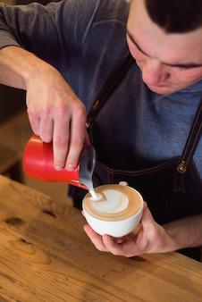 Barista servindo leite na xícara de café para fazer latte art.