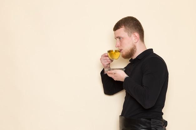 Barista terno preto, bebendo chá quente verde no chão branco