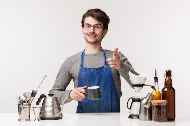 Barista, trabalhador de café e barman conceito. cara caucasiano agradável amigável no avental fazer gesto de pistola de dedo e sorrindo para o cliente enquanto prepara a bebida, fazer café, ficar