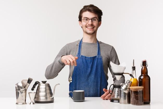 Barista, trabalhador de café e barman conceito. jovem homem caucasiano trabalhando no restaurante, misturando bebidas, em pé perto do bule de chá, chemex, preparar café de filtro