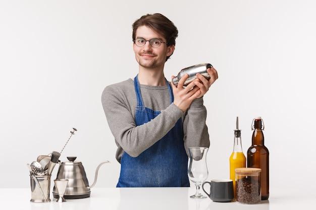 Barista, trabalhador de café e barman conceito. o retrato do empregado masculino novo amigável alegre no avental que mistura bebidas que agita o abanador e a câmera de sorriso, faz a ordem do café do cliente,