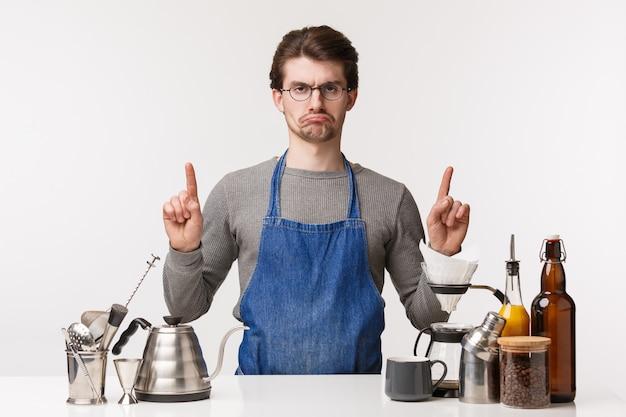 Barista, trabalhador de café e barman conceito. retrato de chateado mal-humorado e descontente jovem empregado masculino, sentindo-se insatisfeito e com ciúmes apontando para cima em pé trabalhando balcão de bar, fazer café