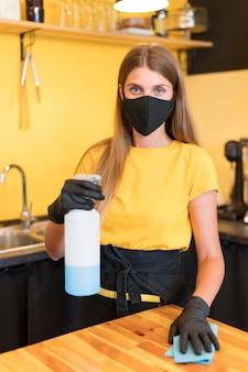 Barista vestindo máscara e desinfecção