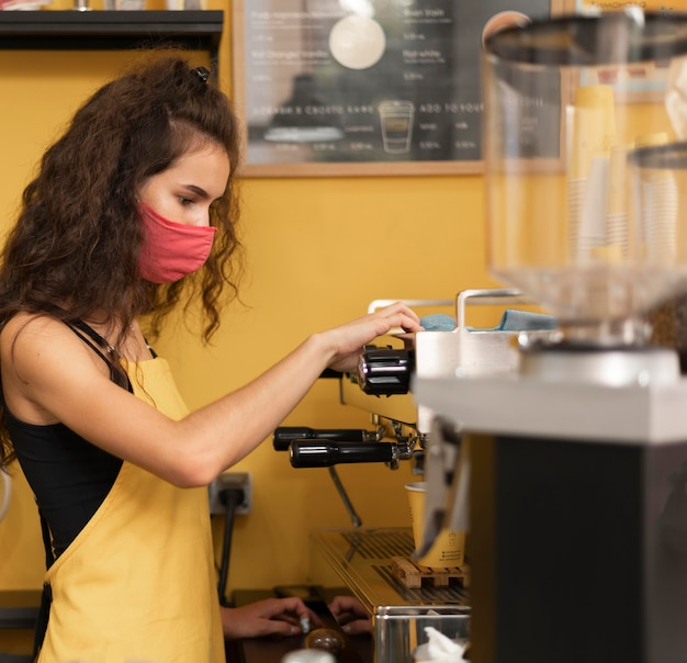 Barista vista lateral usando uma máscara médica enquanto faz café dentro de casa