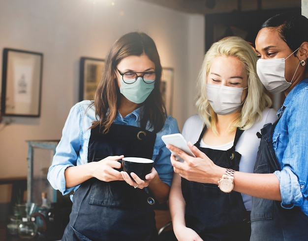 Baristas felizes usando máscaras olhando para um telefone em um café