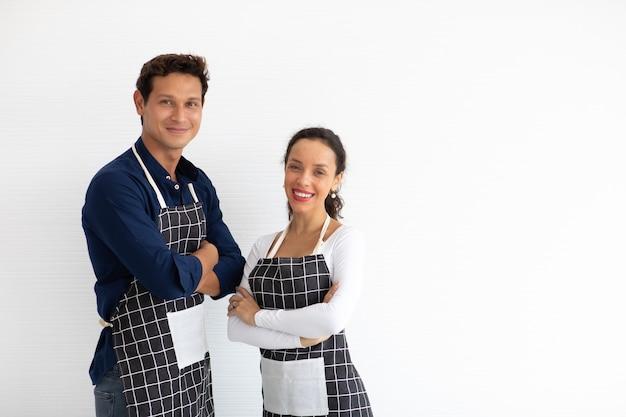 Baristas hispânicos de homem e mulher vestindo avental preto braços cruzados sobre fundo branco.