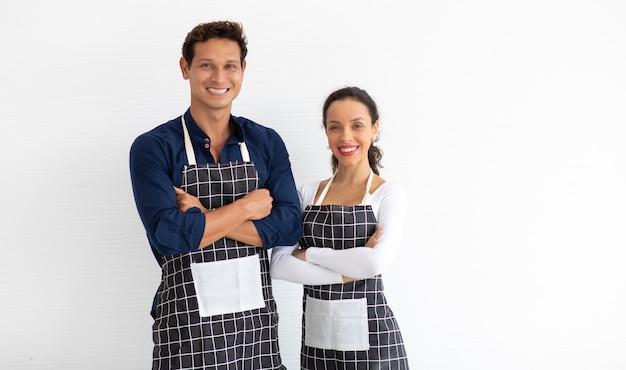 Baristas hispânicos de homem e mulher vestindo avental preto braços cruzados sobre fundo branco. Foto Premium