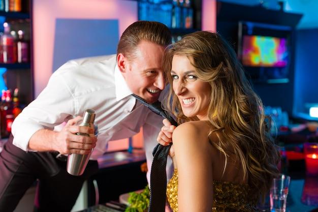 Barkeeper arrastando da mulher no clube ou barra