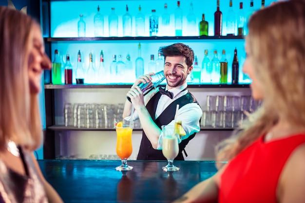 Barkeeper preparando coquetel para clientes do sexo feminino