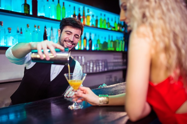 Barkeeper, servindo, coquetel, para, mulher jovem