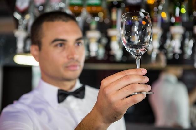 Barkeeper, verificando um copo de vinho após a limpeza