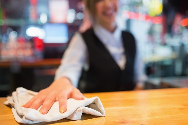 Barmaid bonita limpando bar