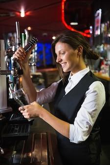 Barmaid feliz puxando uma caneca de cerveja em um bar