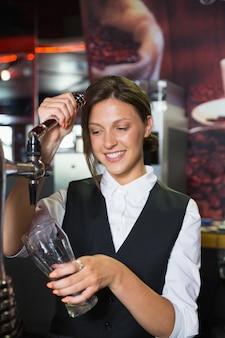 Barmaid feliz puxando uma caneca de cerveja