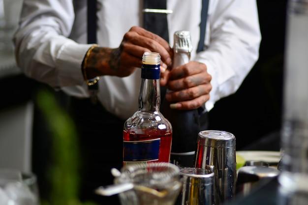 Barman abre uma garrafa de bolha, barman profissional fazendo uma bebida em um bar