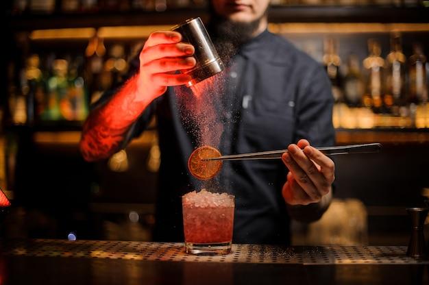 Barman adicionando a uma bebida no copo uma laranja seca com uma pinça e pó aromático no balcão do bar