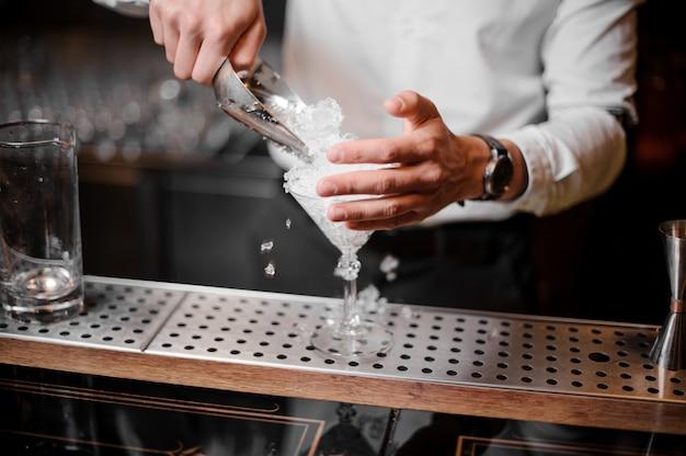Barman, adicionando gelo picado em um copo vazio