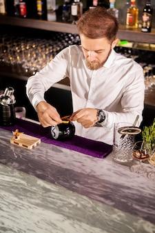 Barman adicionando ingredientes do coquetel. barman no interior do bar fazendo coquetel de álcool.