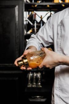Barman, agitando um cocktail em uma coqueteleira de vidro