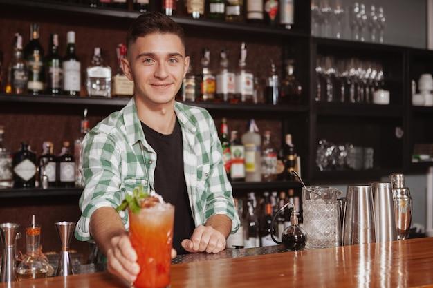 Barman alegre bonito desfrutando de trabalhar no seu bar, servindo um delicioso cocktail, copie o espaço