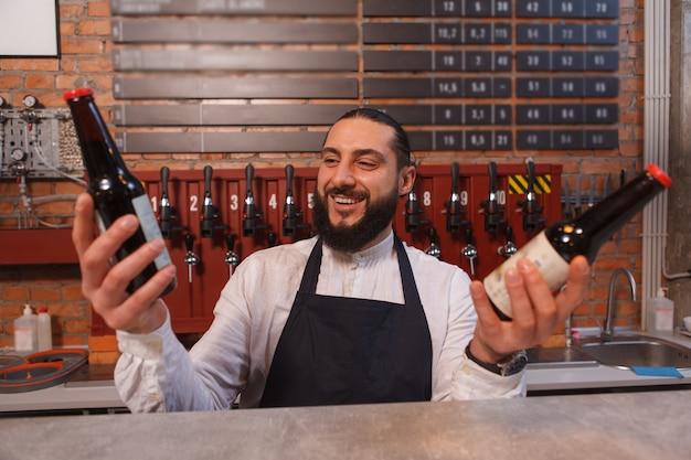 Barman alegre escolhendo entre duas garrafas de cerveja que está segurando