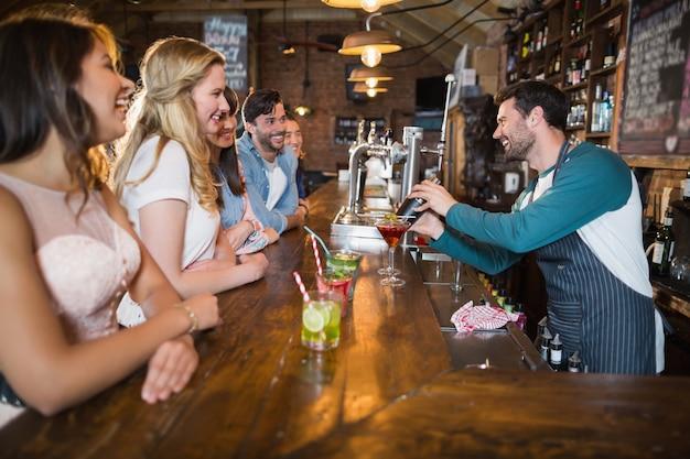 Barman alegre interagindo com os clientes enquanto faz a bebida