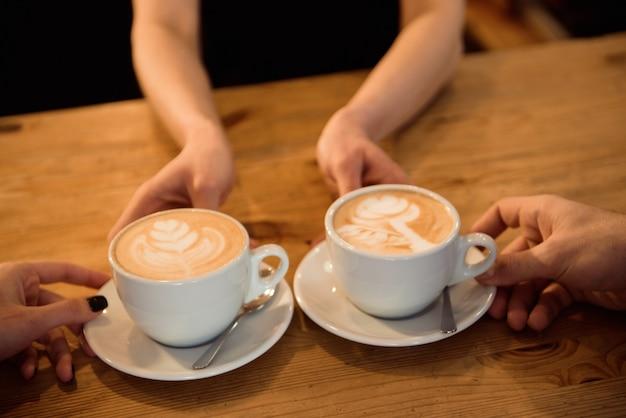 Barman amigável que serve café expresso a clientes no interior de uma cafeteria moderna.