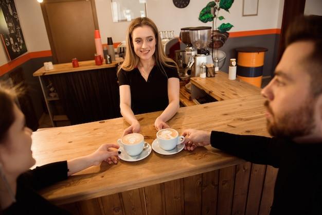 Barman amigável que serve o café do café aos clientes no interior de uma cafetaria moderna.