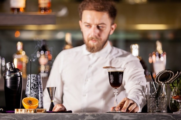 Barman apresentando coquetel de café no lounge bar. boa atmosfera