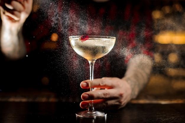 Barman aspersão amargo no elegante copo de cocktail