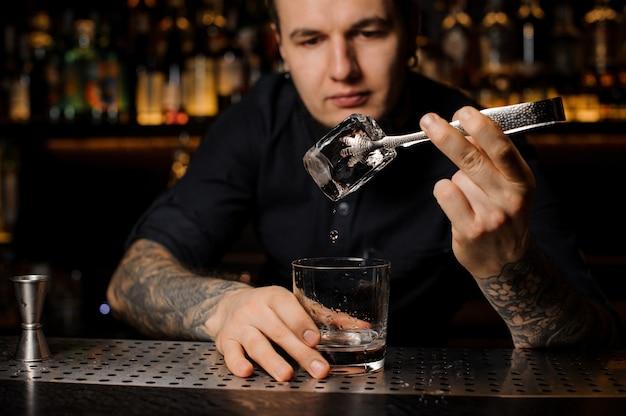 Barman atraente adicionando a uma bebida no copo um grande cubo de gelo com uma pinça no balcão do bar