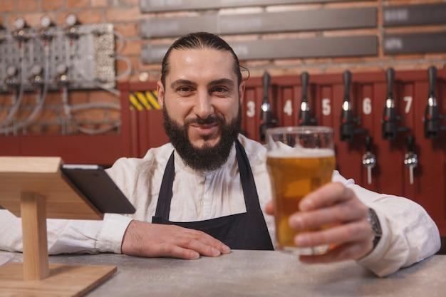 Barman barbudo alegre segurando um copo de cerveja sorrindo