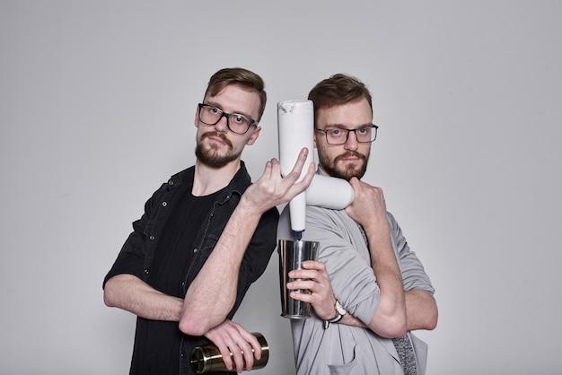 Barman barbudo bonito gêmeos malabarismo com agitador e garrafas na parede cinza