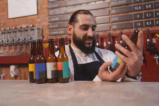Barman barbudo examinando a garrafa de cerveja em suas mãos, trabalhando em seu pub