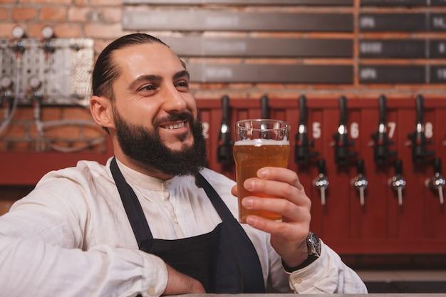 Barman barbudo feliz desfrutando de uma cerveja deliciosa em seu pub