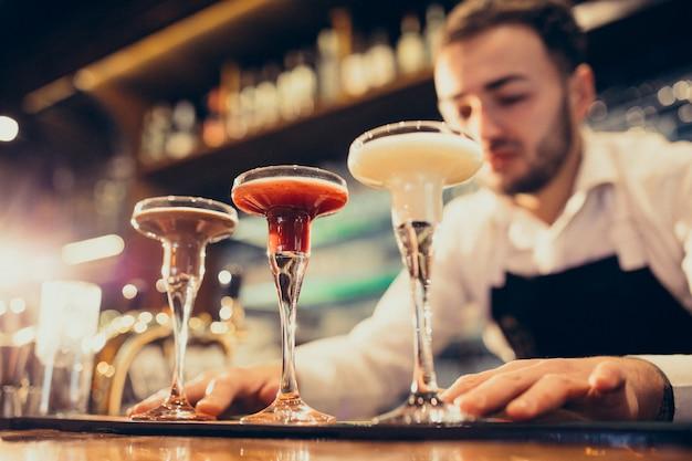 Barman bonito fazendo beber e cocktails num balcão