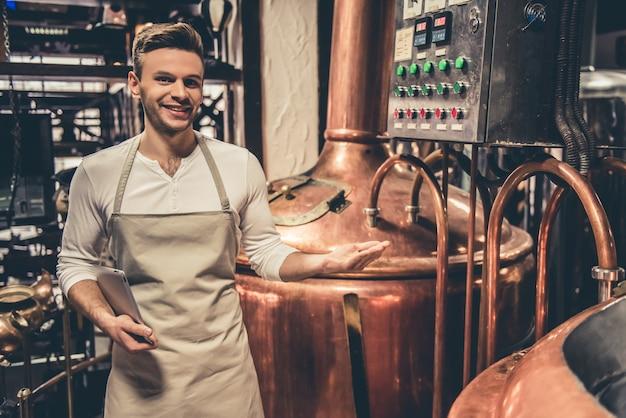 Barman bonito no avental está segurando uma pasta.
