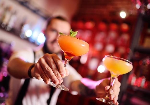 Barman bonito prepara um cocktail alcoólico laranja e sorri na superfície de um bar ou uma boate