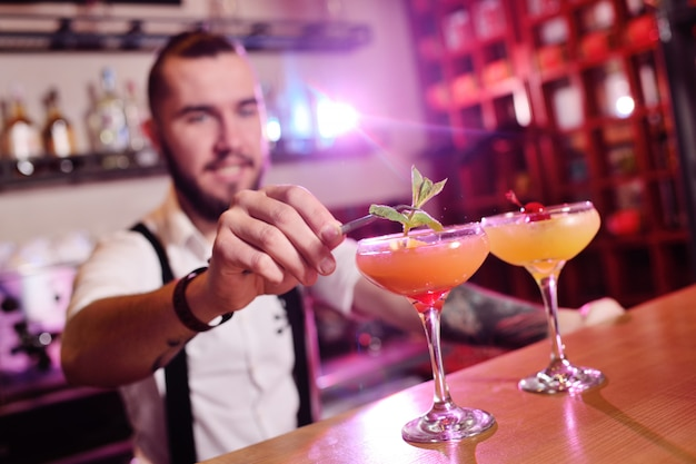 Barman bonito prepara um coquetel alcoólico laranja e sorrisos de um bar ou um clube noturno