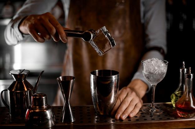 Barman, colocando um cubo de gelo grande com uma pinça para o shaker de aço
