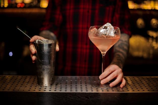 Barman com agitador e copo com coquetel doce fresco e saboroso